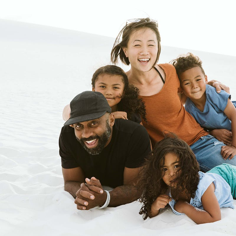 The Register Family, man and woman with three kids, lay in white sand and smile at the camera.