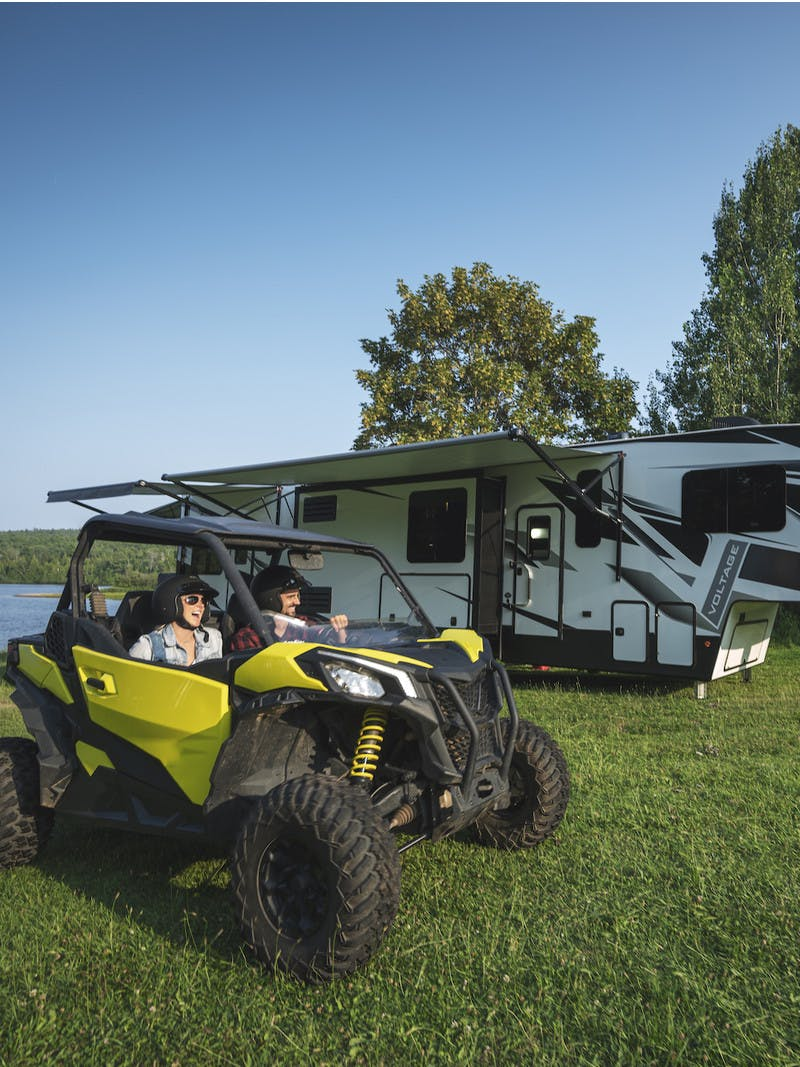 Couple rides a side-by-side hauled by a toy hauler RV at a campsite by the lake