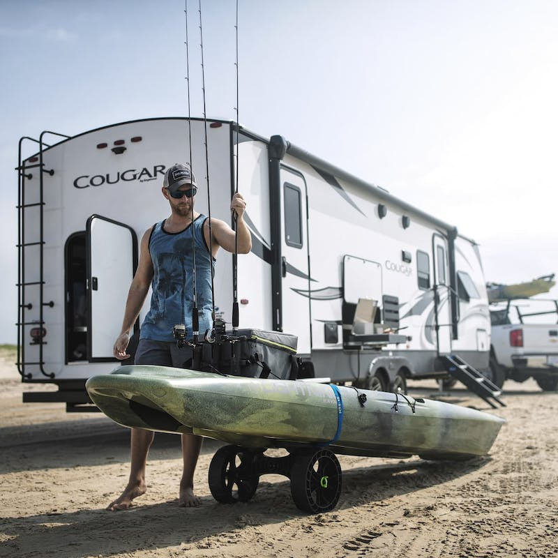 Fisherman stands on beach, in front of Keystone Cougar RV, loading kayak with fishing poles
