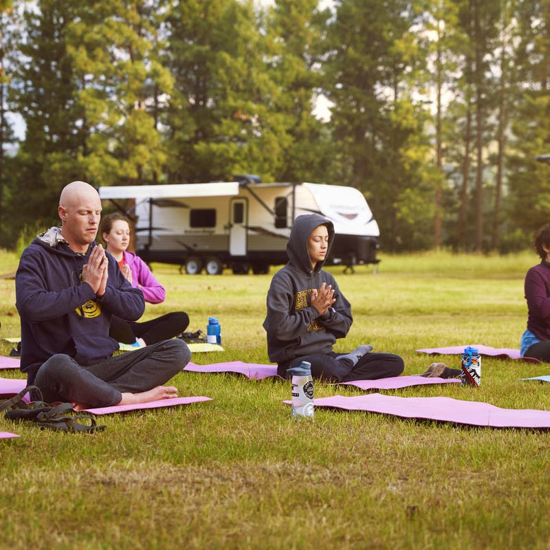 A group of participants sits with their legs folded while practicing yoga outside of the travel trailers where they sleep.