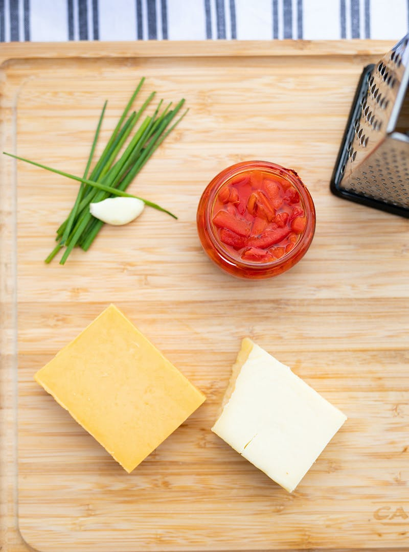 A cutting board with chives, garlic, cheese and a jar of pimentos on it.