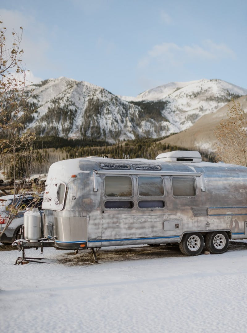 Airstream in the snow with snowy mountains in the background
