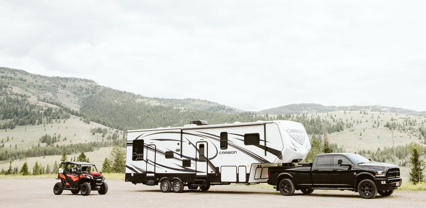A fifth wheel toy hauler parked next to a side by side.