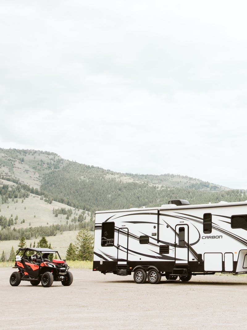 A fifth wheel toy hauler RV parked next to a side by side.