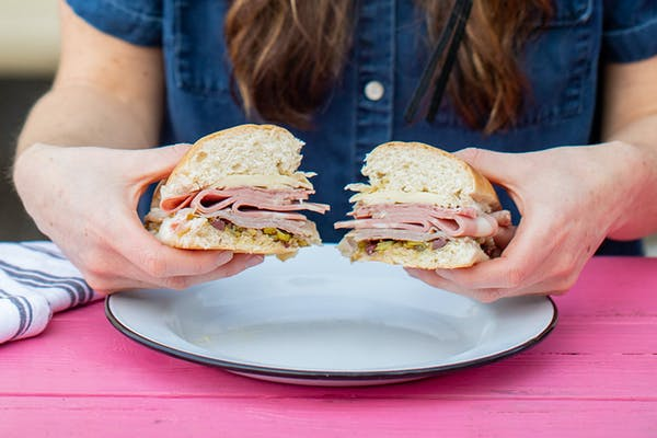 A woman holding a muffaletta sandwich up to show if off to the camera.