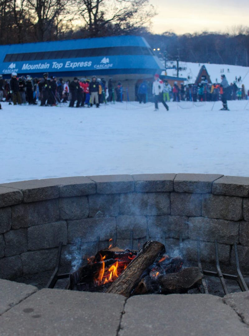 Fire pit at the base of ski hill, with ski lift line in the background