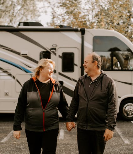 A couple holding hands in front of an RV.