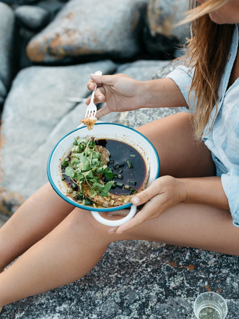 Close up of woman's legs, eating fish in brown broth with cilantro and a fork.