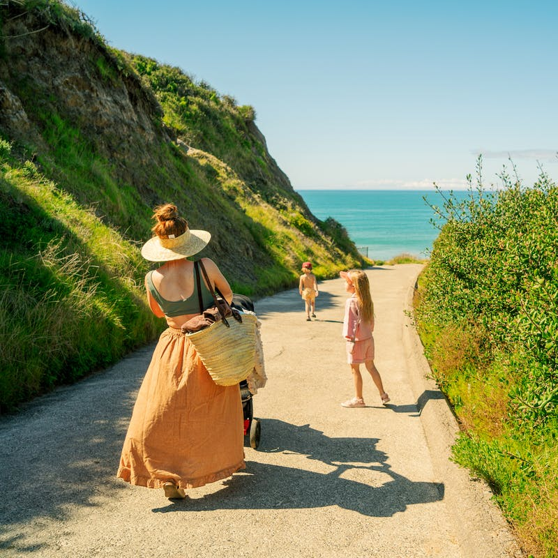 Mom in orange skirt pushes stroller down paved road with two kids and ocean in background