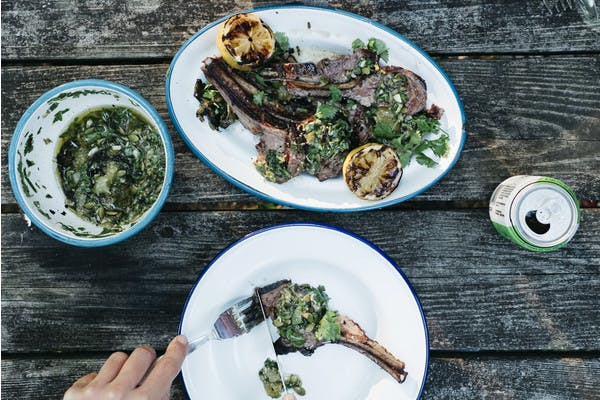 A plate of lamb with lemons and tomatillo sauce over the top.