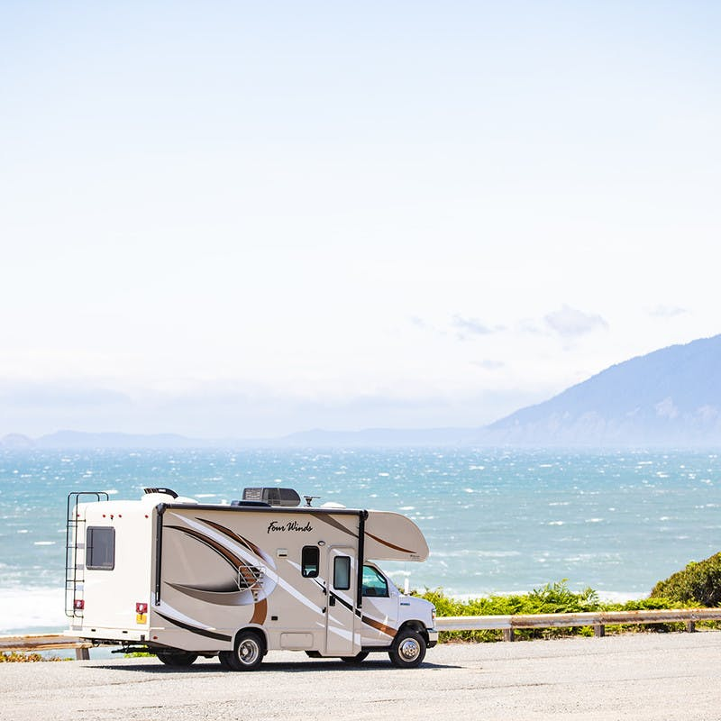 Class-C motorhome in front of ocean beach, along road, with mountain in the fog.