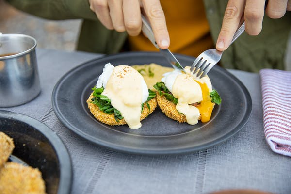 Yolk oozing out of an egg on top of fried green tomatoes.