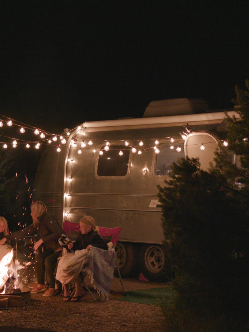 Family sitting around fire in front of Airstream, hung lights.