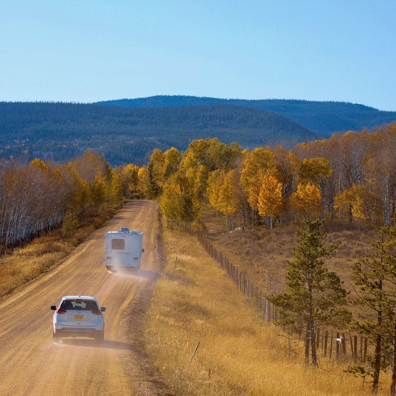 White car and Class C RV on dusty dirt road heading into forest of yellow trees