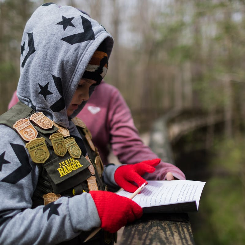 Desiree Walters' son reading out of a booklet to earn a Junior Ranger badge.
