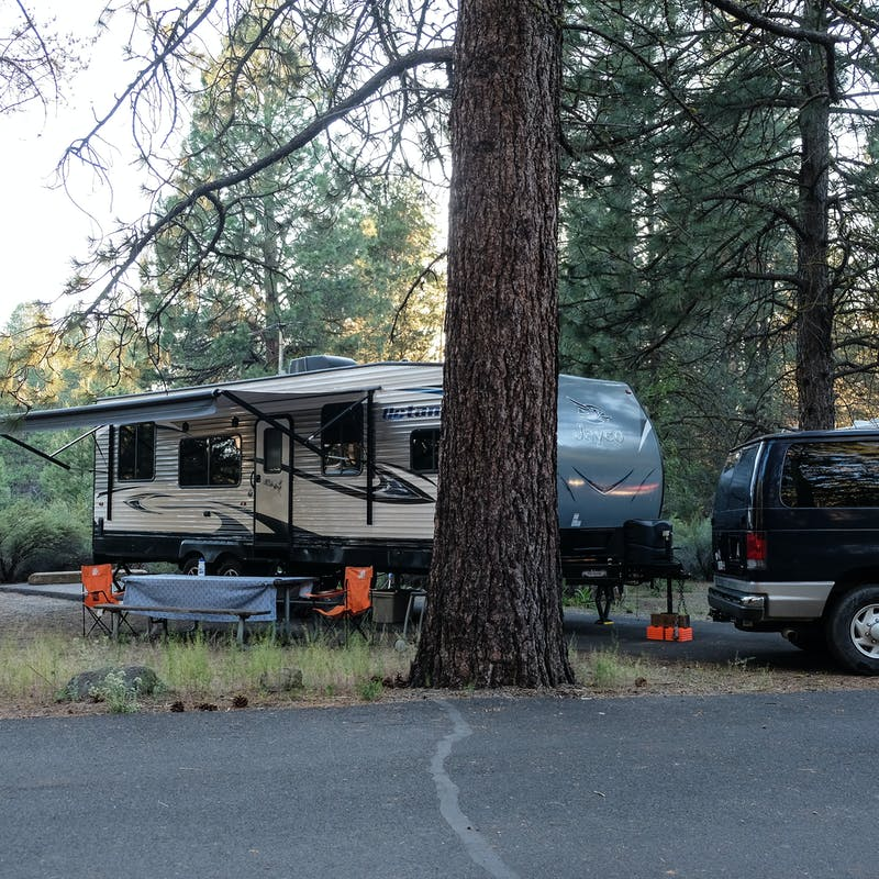Gretchen Holcomb's Jayco Octane toy hauler parked in a wooded campsite.