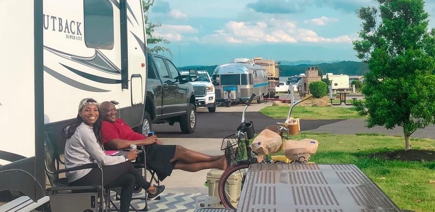 A couple relaxes outside their RV in camping chairs
