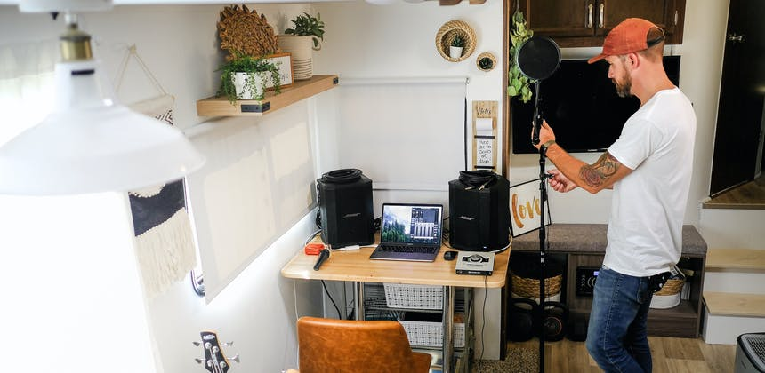 Amick Cutler sets up recording equipment inside his RV by a desk.