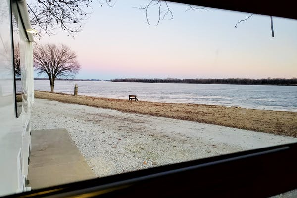 A photograph out an RV window onto a wintry lake.