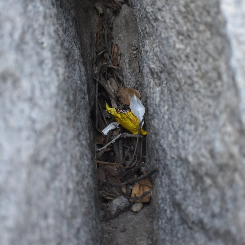 Piece of yellow trash hidden within two rocks