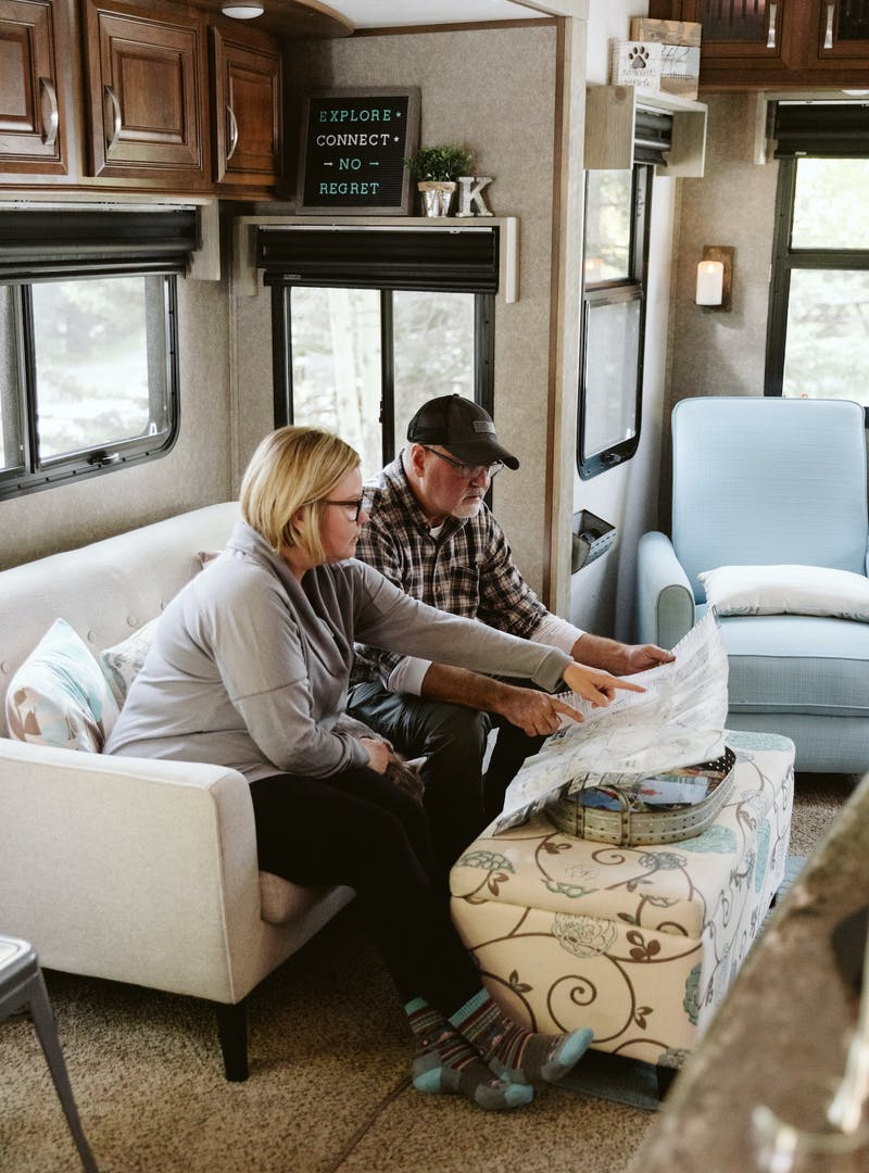 Tina and Craig sitting on a couch inside their RV, looking at a map.