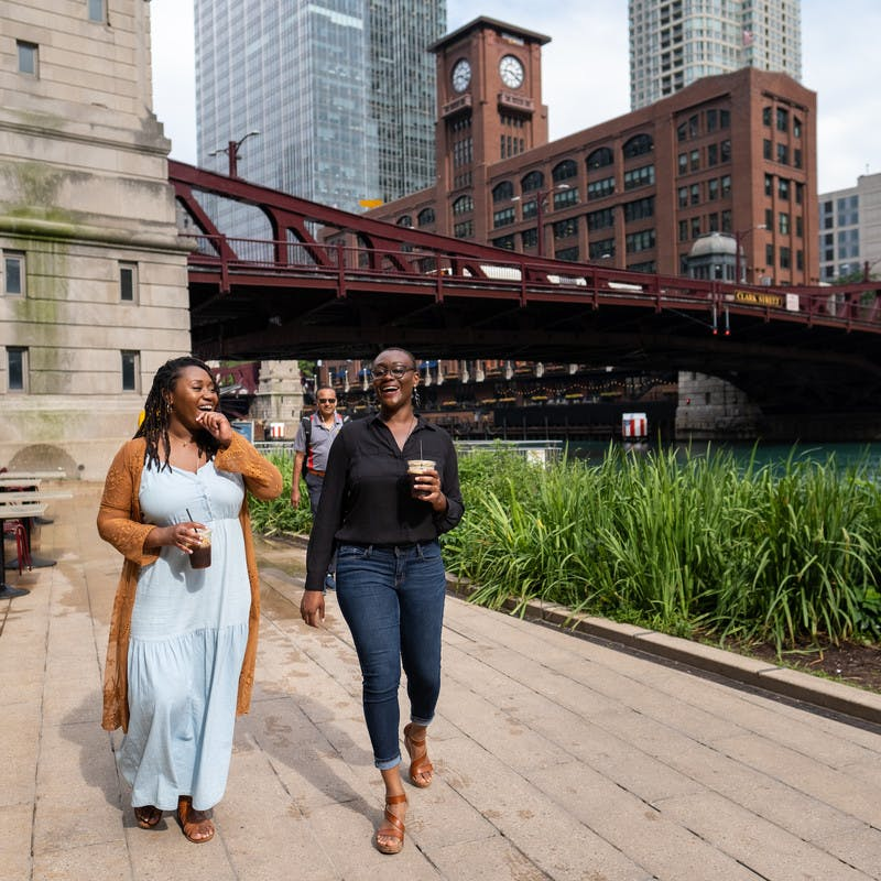 Chanel and Brittany Tate walking along the Chicago riverfront drinking coffee and talking.