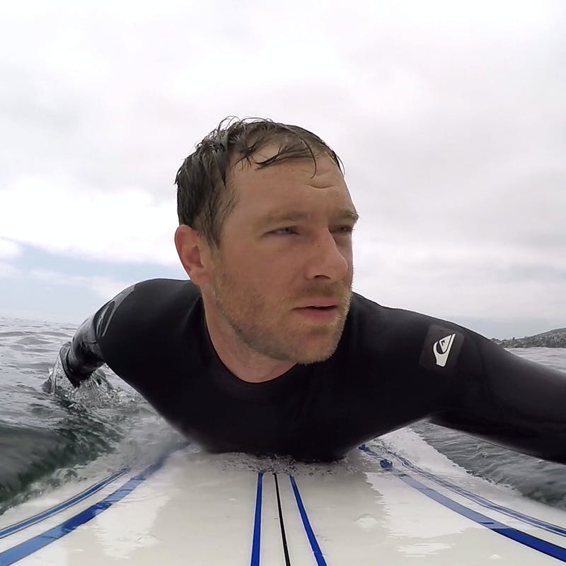 Eric Hannan paddling out to surf.
