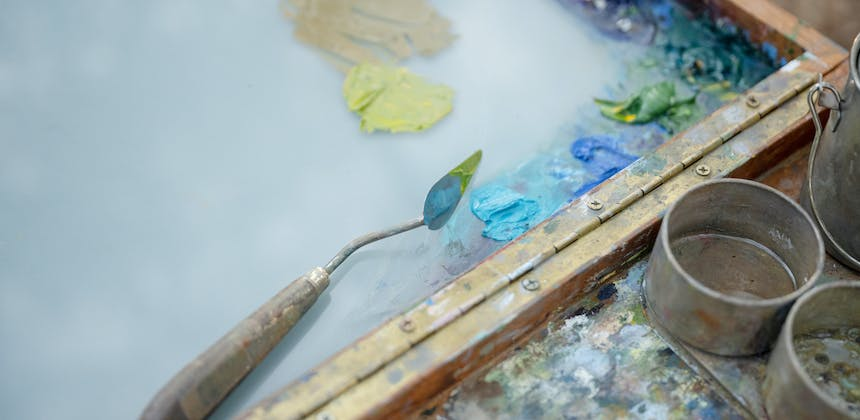 A board with blue, green and yellow paint used to paint a landscape.