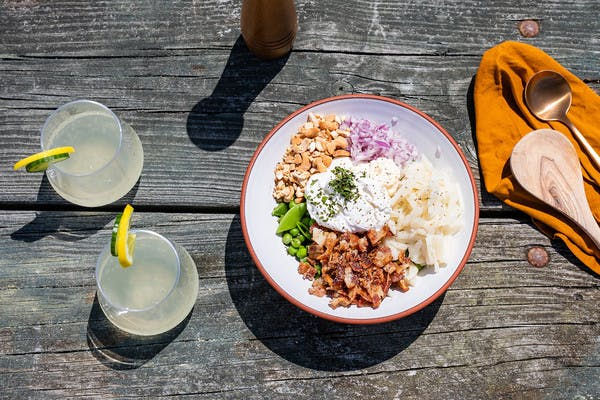 White bowl on picnic table filled with peas, bacon, red onion, water chestnuts, cashews, and sour cream, with two glasses of lemonade.