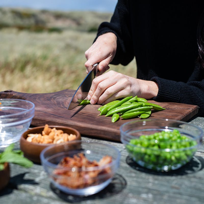 Picnic table with small glass bowls, and a woman slicing snap peas on a cutting board.