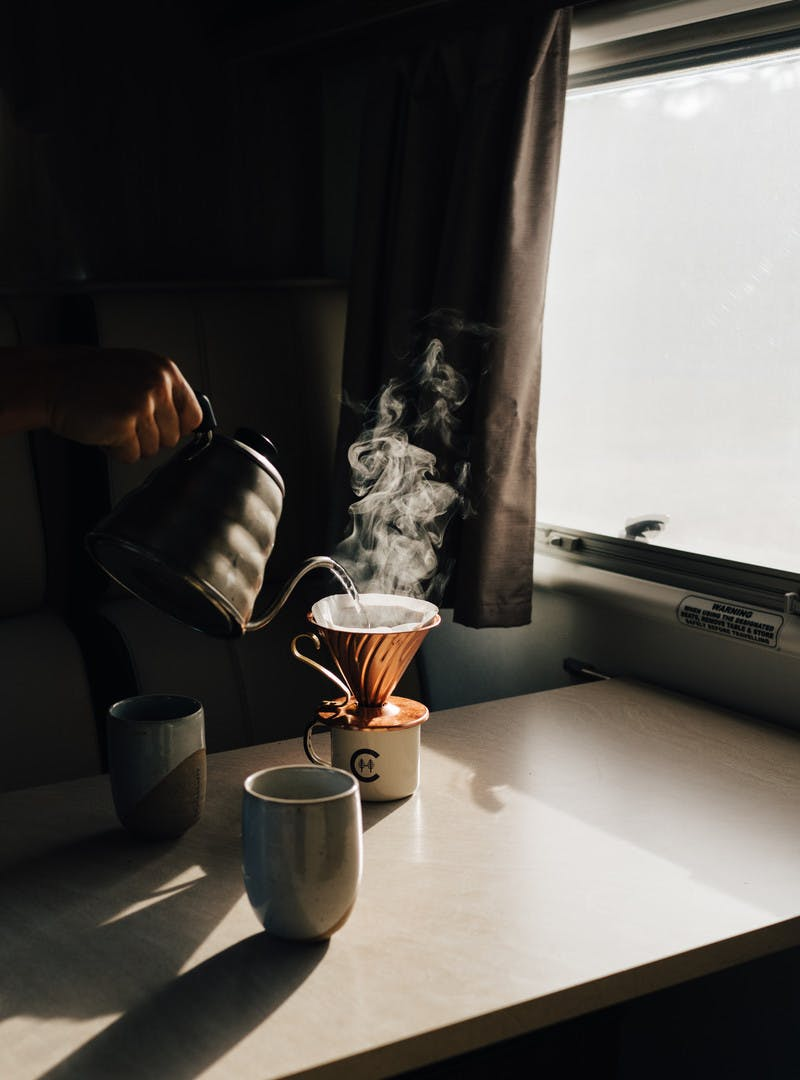 Next to a window, a shadowy shot of a hand pouring water out of a kettle over coffee grounds inside a Class C motorhome.