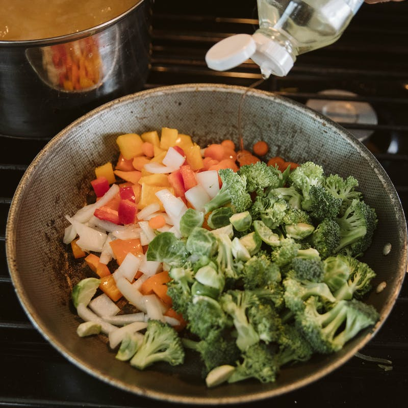A saute pan full of cooking vegetables.