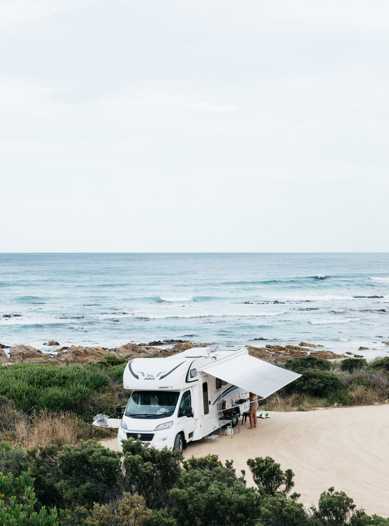 A Class C motorhome parked on the beach next to the ocean with a beautiful view.