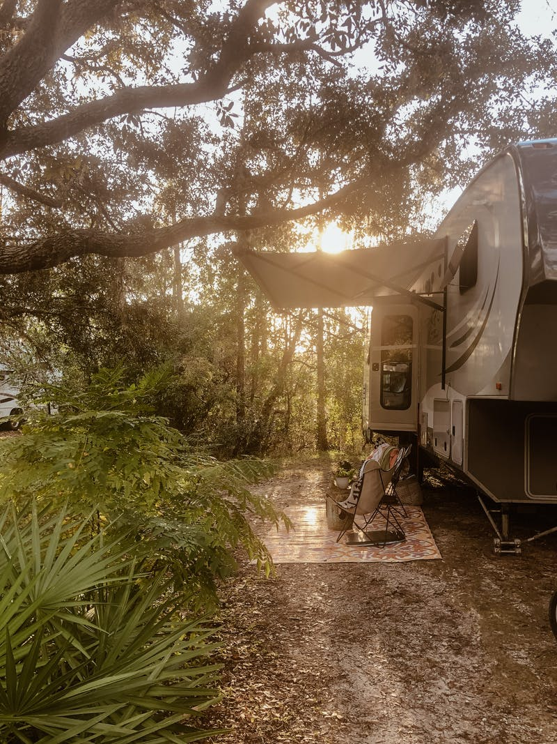 Shannon Carew's Highland Ridge RV parked at a leafy campsite.