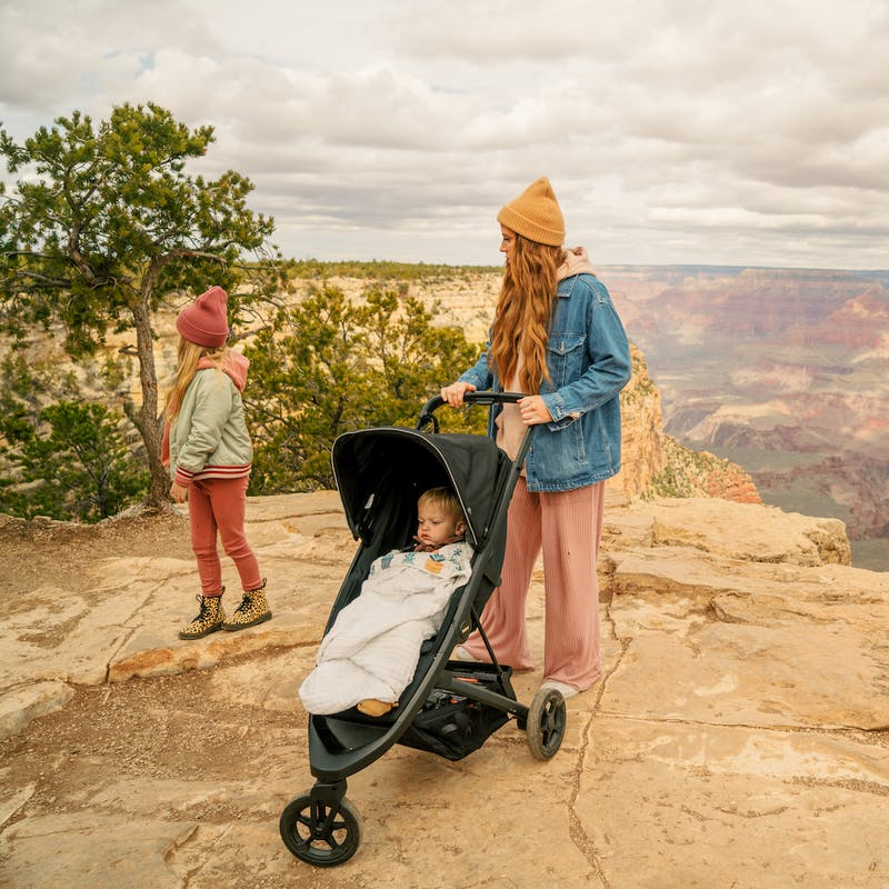Women in yellow hat pushes stroller with little girl standing next to her on edge near Grand Canyon