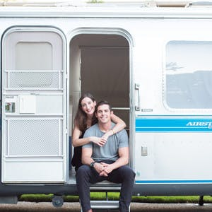 Image of Christina and Mack Griffin sitting in the doorway of their Airstream Travel Trailer RV.