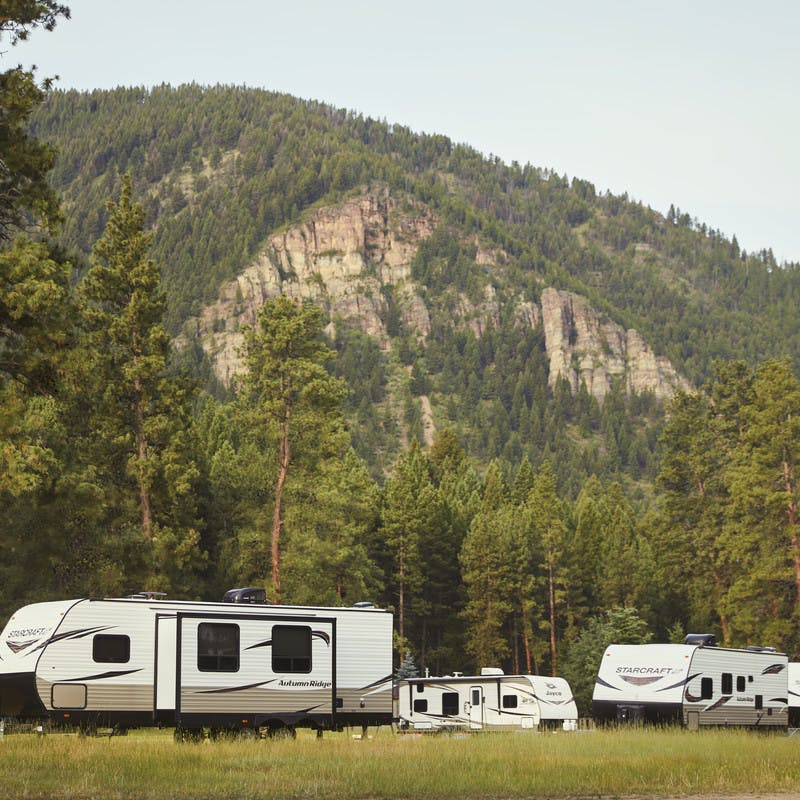 Travel trailers sit in front of a mountain on Cliffs Ranch near the Blackfoot River in Montana.