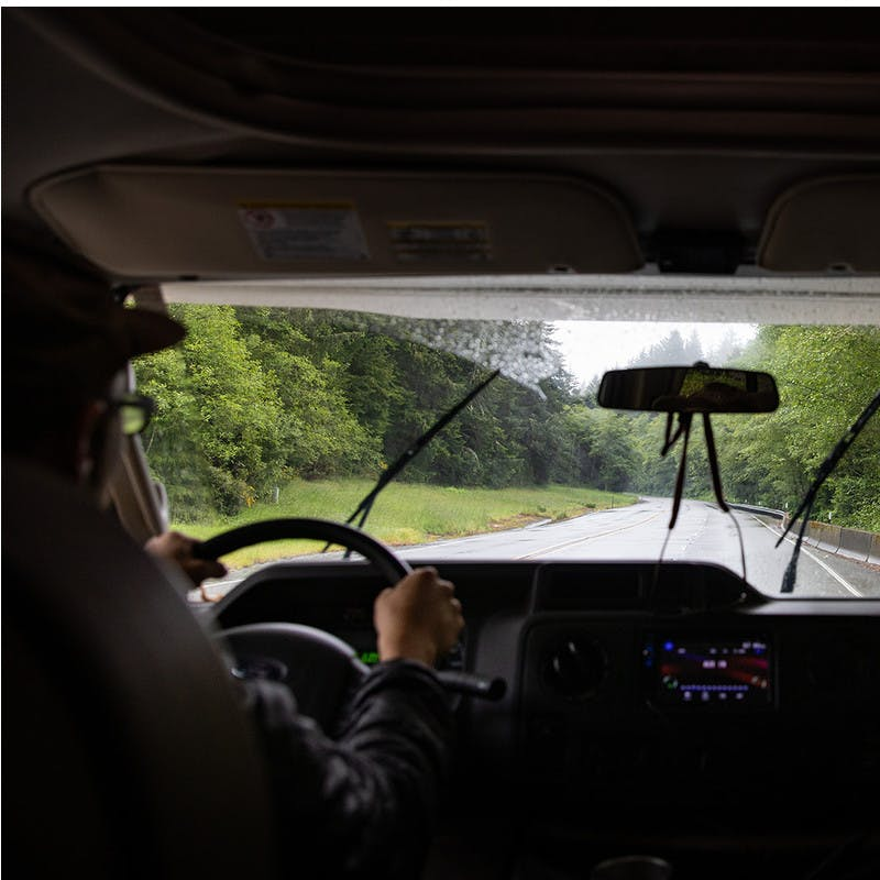 View out front windshield of motorhome onto road and forest with windshield wipers.