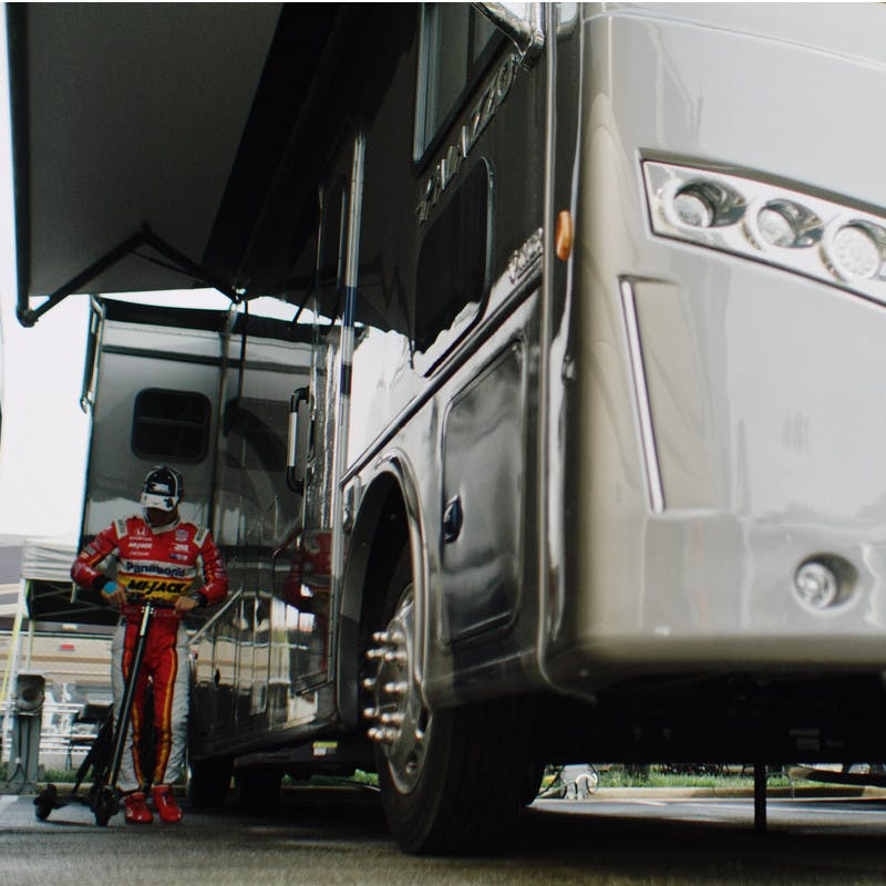 Takuma Sato stands with his scooter next to his Class A Thor Motor Coach RV.