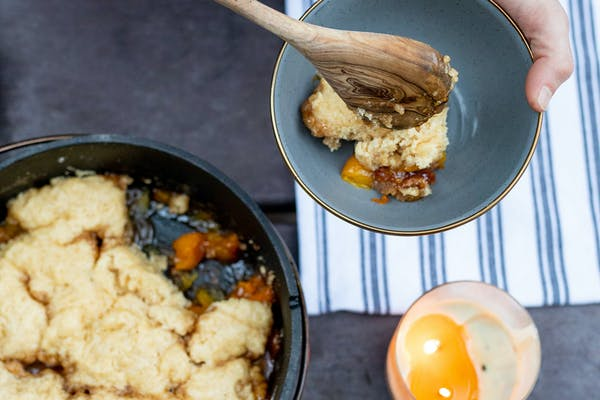 Serving up hot peach cobbler into a bowl with a wooden spoon.