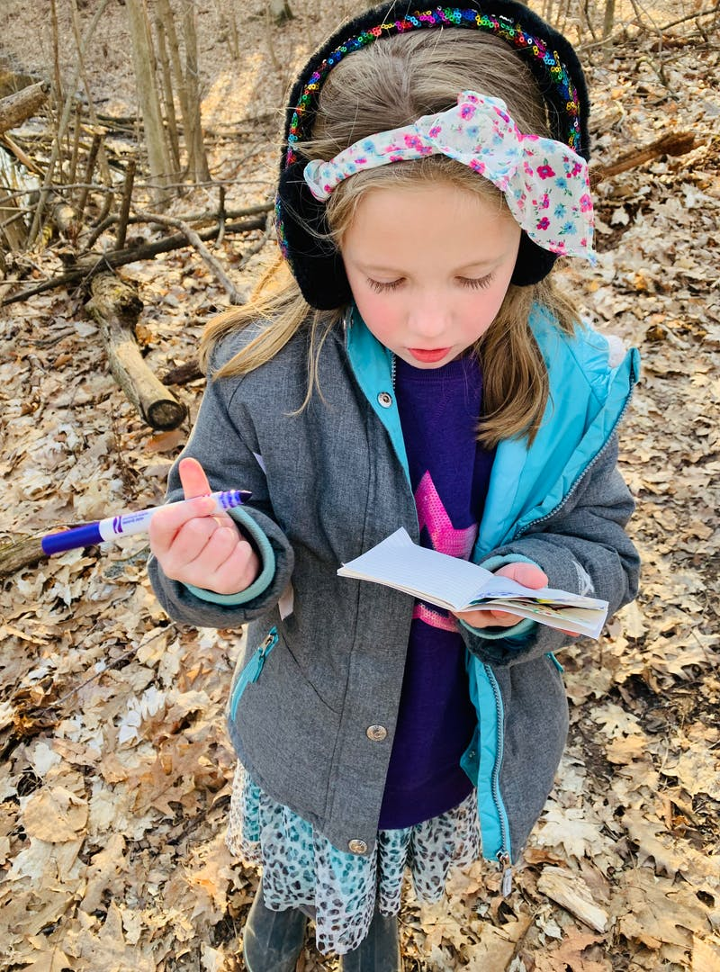 Young girl with headband and earmuffs holds purple marker and notepad in the forest