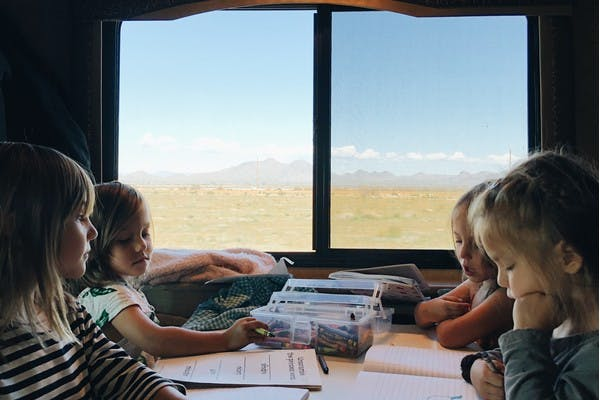 Four young kids sitting at an RV table playing and coloring, with desert mountains out the window.