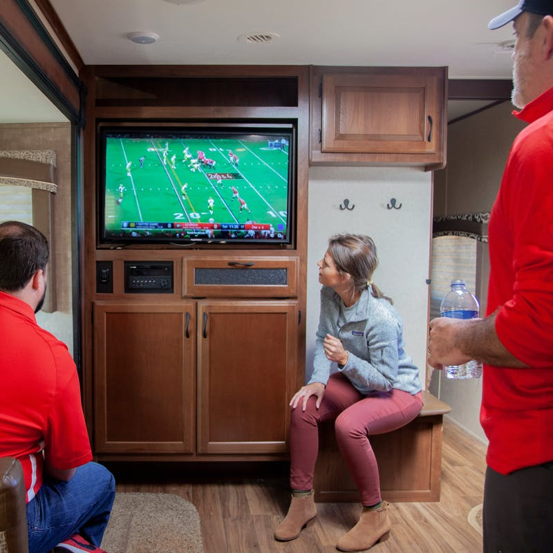 Group of friends watching sports on the RV tv.