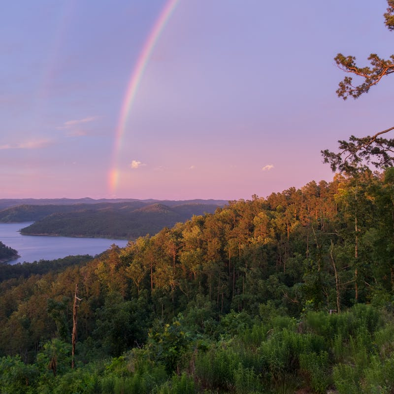 A Brilliant Rainbow at Sunset over Mountain Lake in Beavers Bend State Park