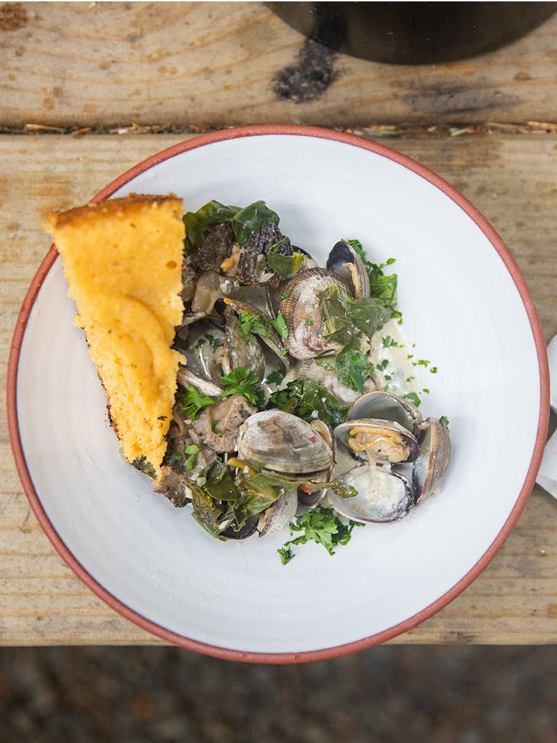 Bowl of cooked clams with parsley on a white plate, a golden slice of cornbread, and gold utensils on a white napkin.