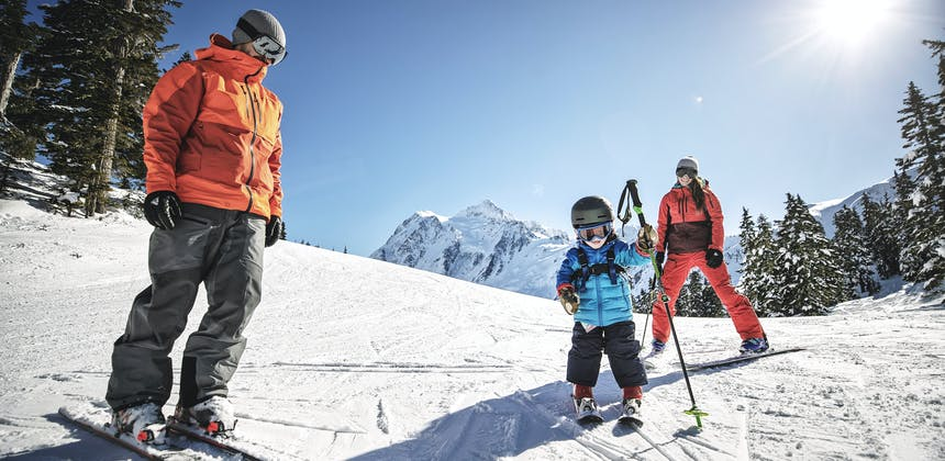 A small child stands on skis with his parents in Mt. Baker, Washington.