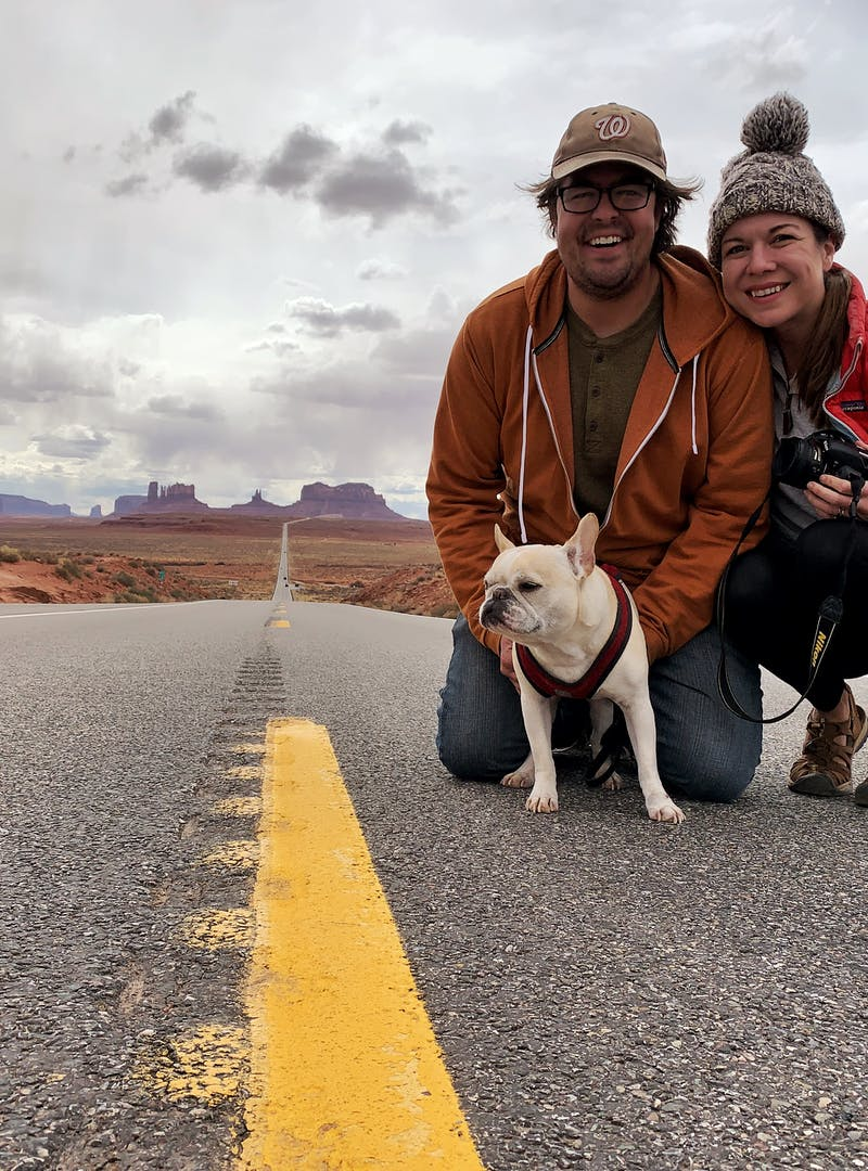 Sarah Hubbart, her husband and their dog take a photo in the road in the desert.