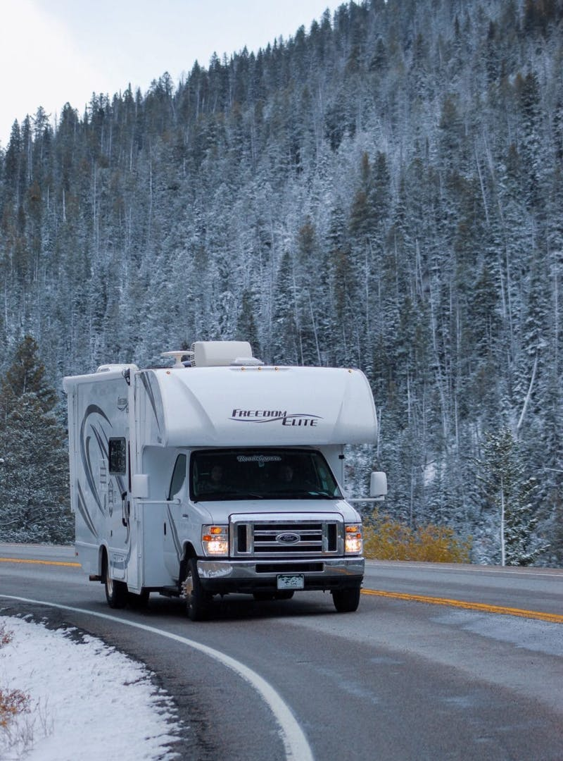 Class C RV drives along windy, snowy mountain road