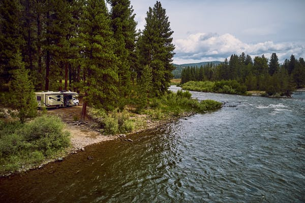 A Class C RV sits next to a bank on the Blackfoot River in Montana.