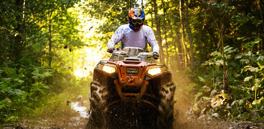 A man ATVs through a muddy forest trail.